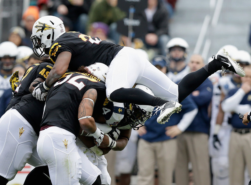 . Chris Young #21 of the Arizona State Sun Devils jumps on the pile to stop Noah Copeland #34 of the Navy Midshipmen during the Kraft Fight Hunger Bowl at AT&T Park on December 29, 2012 in San Francisco, California.  (Photo by Ezra Shaw/Getty Images)