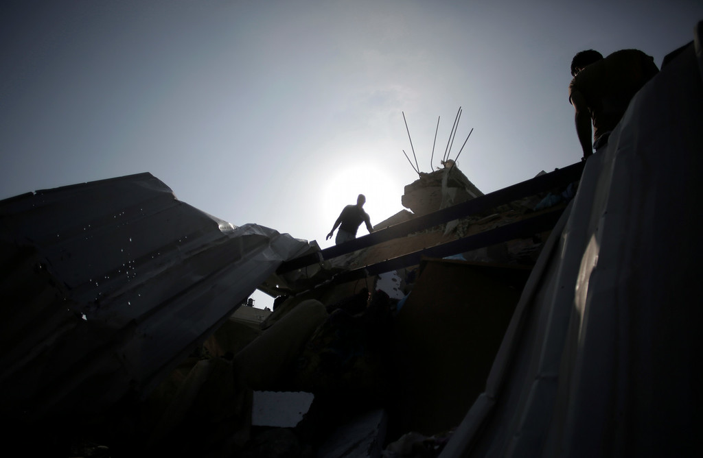 . Palestinians inspect the damage of their house after it was destroyed in an Israeli strike late Friday, in Gaza City, Saturday, Aug. 23, 2014. (AP Photo/Khalil Hamra)