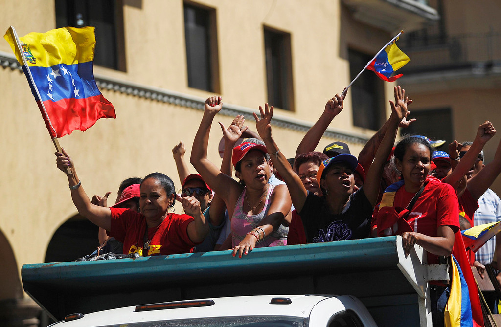 . Supporters of Venezuela\'s late President Hugo Chavez ride on a truck to follow his coffin as it is driven through the streets of Caracas, March 6, 2013. REUTERS/Jorge Dan Lopez