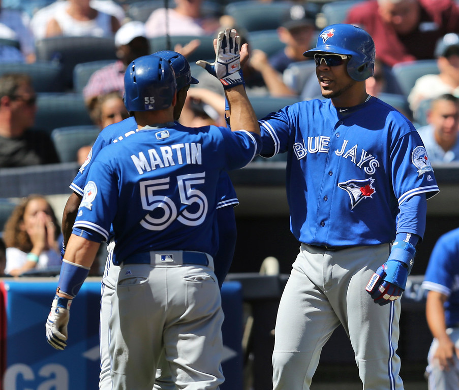 . Toronto Blue Jays\' Edwin Encarnacion, right, greets Russell Martin and other teammates after they scored on a home run hit by Melvin Upton Jr. during the fifth inning of the baseball game against the New York Yankees at Yankee Stadium, Wednesday, Aug. 17, 2016 in New York. (AP Photo/Seth Wenig)