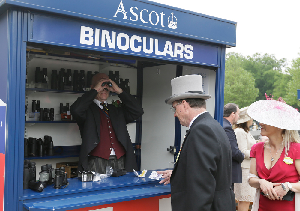 . A race goer hires a pair of binoculars from a stall holder who checks them on the first day of the Royal Ascot horse race meeting in Ascot, England, Tuesday, June 18, 2013. (AP Photo/Alastair Grant)