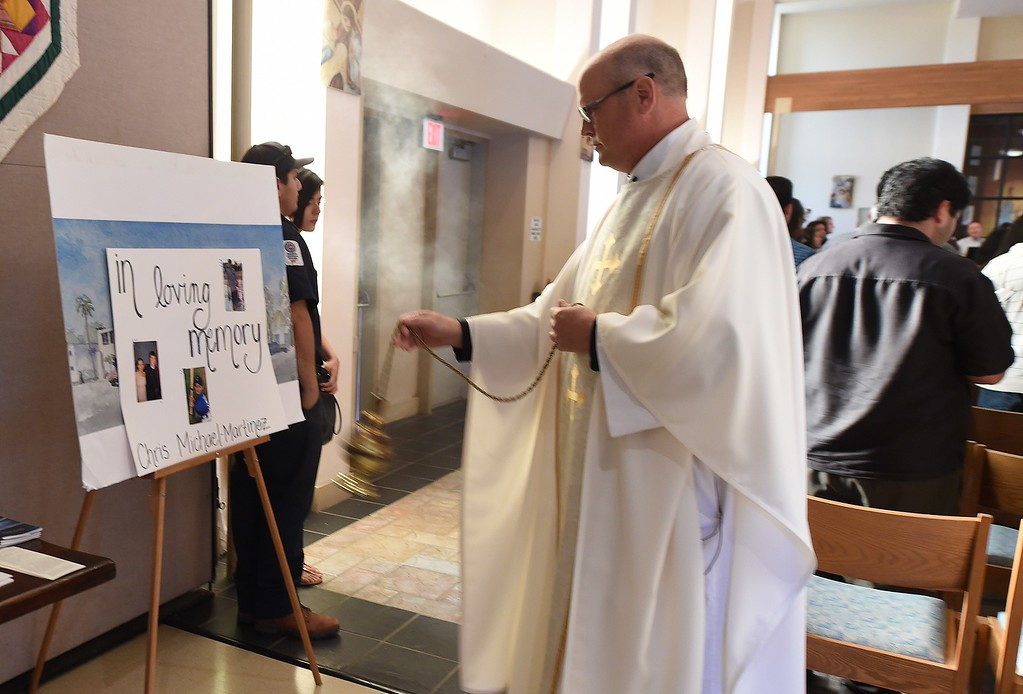 . Father John Love waves incense in prayer over photos of shooting rampage victim Chris Michael-Martinez, at a memorial service for those killed in a mass shooting believed to be perpetrated by Elliot Rodger, at St. Marks University Parish in Isla Vista, California, May 25, 2014.  Seven people we killed and 13 injured in the May 23 incident.           (ROBYN BECK/AFP/Getty Images)