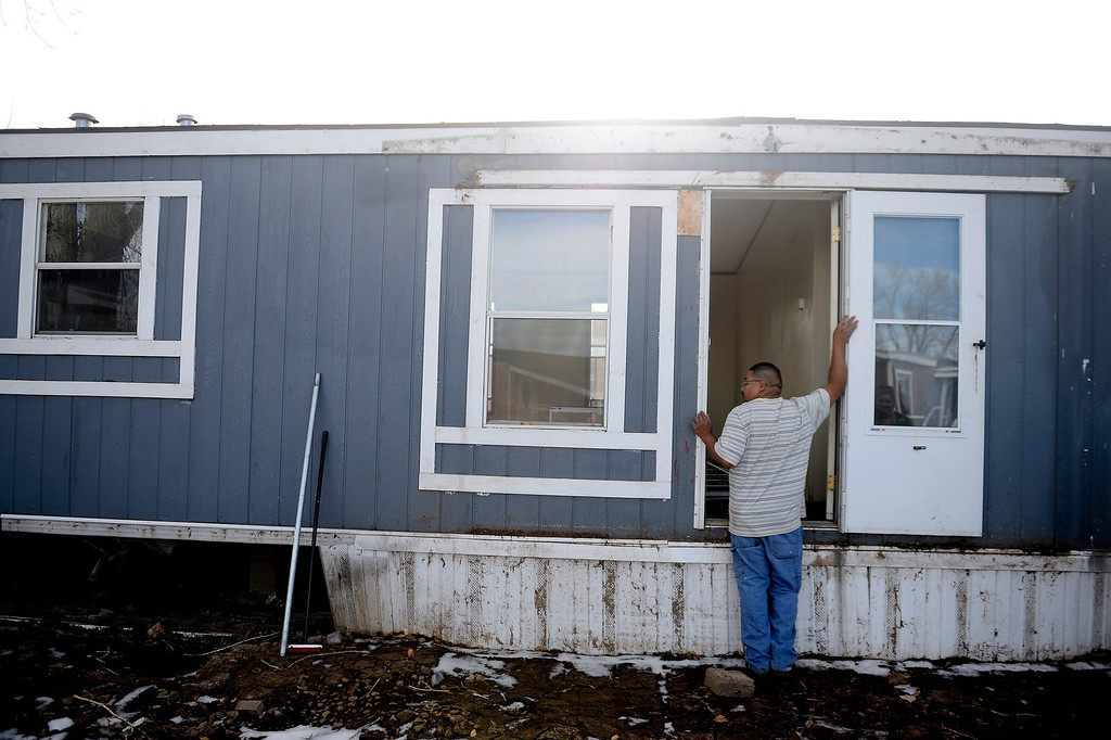 . MILLIKEN, CO - DECEMBER 18: Jorge Neveo looks into his sister Laura Medina\'s flooded mobile home as he helps her with tearing out carpet and other damaged surfaces. Residents of the mobile home park say that the city of Milliken has not done enough to assist in the rebuilding of the 33-unit residential sub division that was struck hard by recent floods that ravaged much of northern Colorado. (Photo by AAron Ontiveroz/The Denver Post)