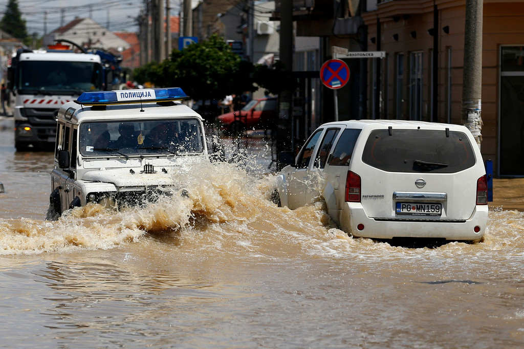 . Serbian, left and Montenegro police cars drive through flooded street in Obrenovac, some 30 kilometers (18 miles) southwest of Belgrade, Serbia, Tuesday, May 20, 2014. Serbia, Bosnia and Croatia have been hit by the worst flooding in more than 100 years, forcing half a million people out of their homes and leading to more than three dozen deaths. (AP Photo/Darko Vojinovic)