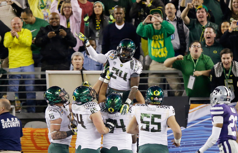 Description of . Kenjon Barner #24 of the Oregon Ducks celebrates his second quarter touchdown against the Kansas State Wildcats with teammates during the Tostitos Fiesta Bowl at University of Phoenix Stadium on January 3, 2013 in Glendale, Arizona.  (Photo by Ezra Shaw/Getty Images)