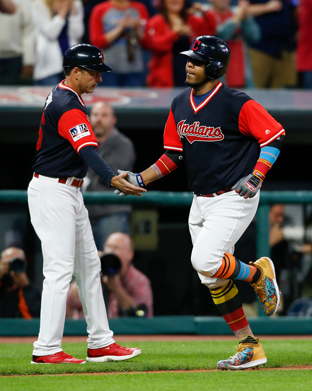 . Cleveland Indians\' Edwin Encarnacion, right, gets congratulations from third base coach Mike Sarbaugh after hitting a solo home run off Kansas City Royals starting pitcher Jason Hammel during the seventh inning in a baseball game, Saturday, Aug. 26, 2017, in Cleveland. (AP Photo/Ron Schwane)