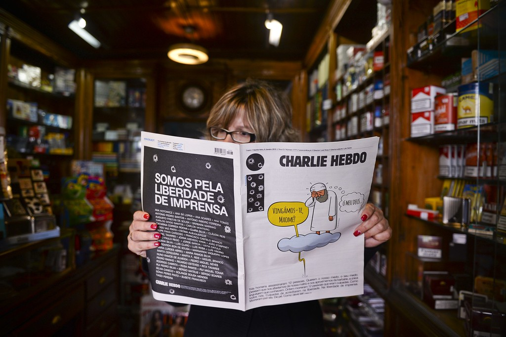 ". A woman reads Portuguese newspaper ""i\"" with the front page picturing a cartoon honoring French newspaper Charlie Hebdo victims after a terror attack yesterday in Paris that left 12 dead, and the back page bearing the inscription \""We are freedom of press\"" in a Kiosk in central Lisbon. AFP PHOTO/ PATRICIA DE MELO  MOREIRA/AFP/Getty Images"