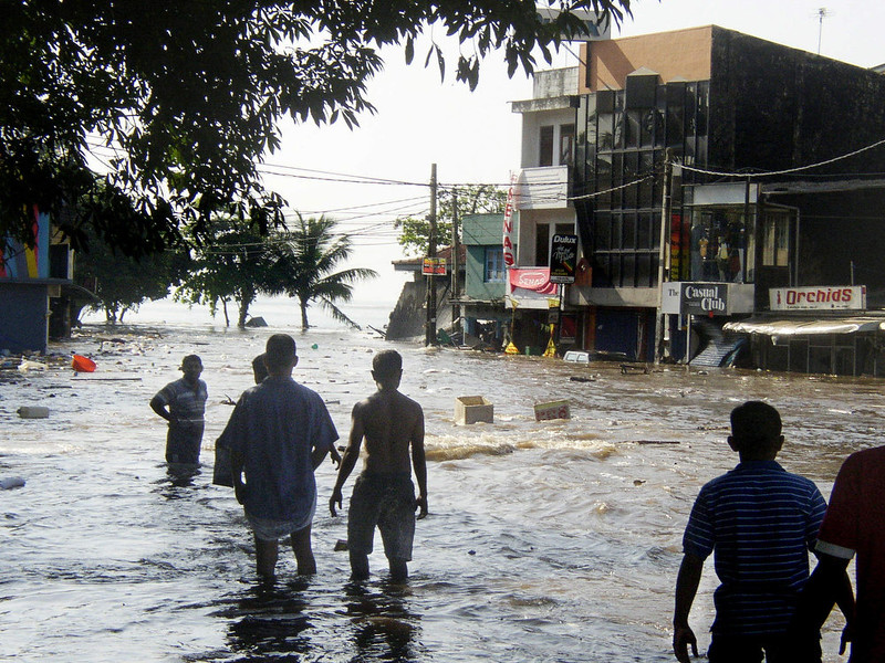 . Sri Lankan pedestrians walk through floodwaters in a main street of Galle, after the coastal town was hit by a tidal wave on December 26, 2004.  At least 70 foreign tourists were among the thousands of people killed in the tidal wave disaster that hit Sri Lanka\'s coastline, tourism director general Kalai Selvam told AFP. At least 4857 people have died in the disaster, while 1555 others are reported missing. The tsunamis were triggered Sunday by a huge earthquake off northeast Indonesia, several thousand kilometers from Sri Lanka. Giant waves also slammed into Thailand, Myanmar, southern India, Malaysia and the Maldives.        STR/AFP/Getty Images