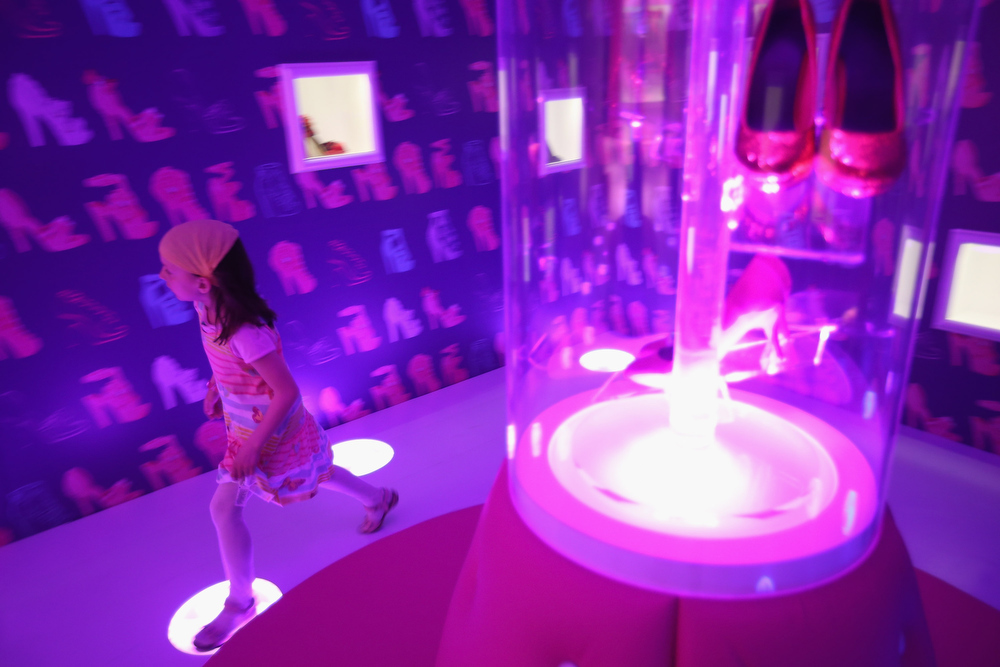 . Amalie, 7, runs through a room of Barbie\'s shoes at the Barbie Dreamhouse Experience on May 16, 2013 in Berlin, Germany. The Barbie Dreamhouse is a life-sized house full of Barbie fashion, furniture and accessories and will be open to the public until August 25 before it moves on to other cities in Europe.  (Photo by Sean Gallup/Getty Images)