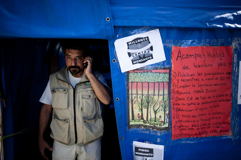 . Activist Oscar Alfredo Di Vincensi talks on a cell phone inside his tent during his one-man hunger strike demanding that agrochemical spraying not be allowed within 1,000 meters of homes, in the main square of Alberti, in Buenos Aires province, Argentina on April 16, 2013. Earlier this year, Di Vincensi stood in a field waving a court order barring spraying within 1,000 meters of homes in his town of Alberti; a tractor driver doused him in pesticide. (AP Photo/Natacha Pisarenko)