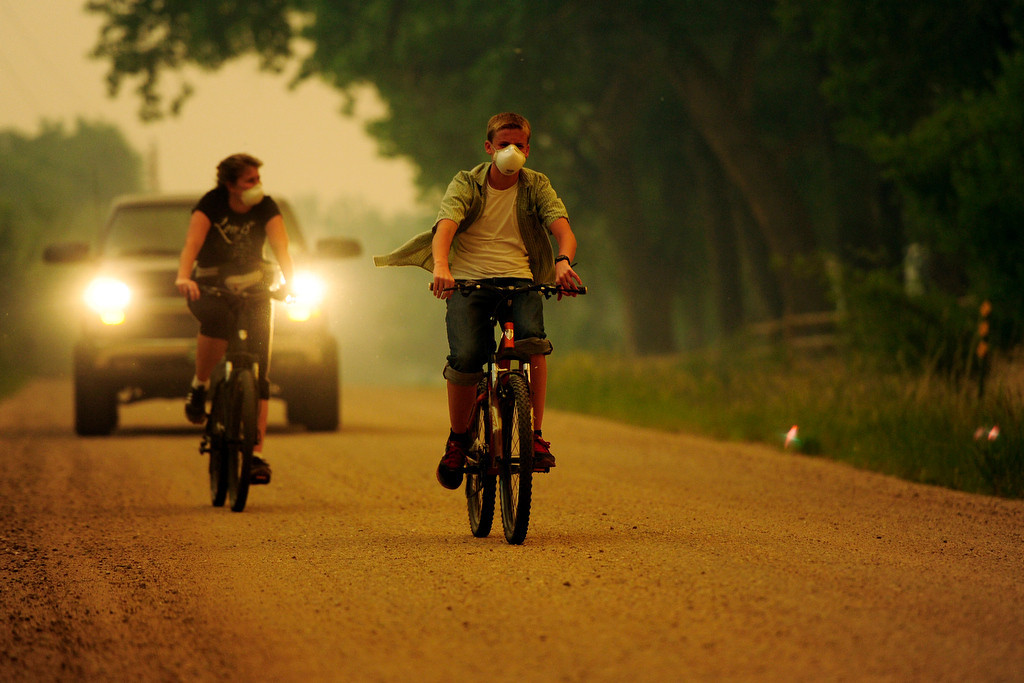. Caleb Armstrong and his mother, Cheryl, ride their bicycles near their home on County Road 56 as the High Park fire burns west of Fort Collins and Loveland on Sunday, June 10, 2012. The rapidly growing High Park fire is now burning an estimated 2,000 to 3,000 acres west of Fort Collins and Loveland, according to the Larimer County Sheriff�s Office. AAron Ontiveroz, The Denver Post