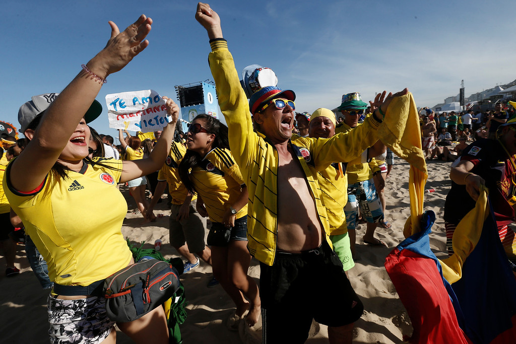 . Colombia soccer fans celebrate their team\'s third goal against Greece as they watch the game inside the FIFA Fan Fest area on Copacabana beach in Rio de Janeiro, Brazil, Saturday, June 14, 2014. Colombia defeated Greece 3-0. (AP Photo/Silvia Izquierdo)