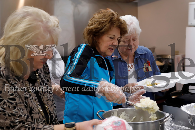 Cindy Simpson (left) and Carol Johnson serve up a to-go box for Anita Negley at Saturday's Thanksgiving for veterans meal at St. Lukes. Seb Foltz/Butler Eagle