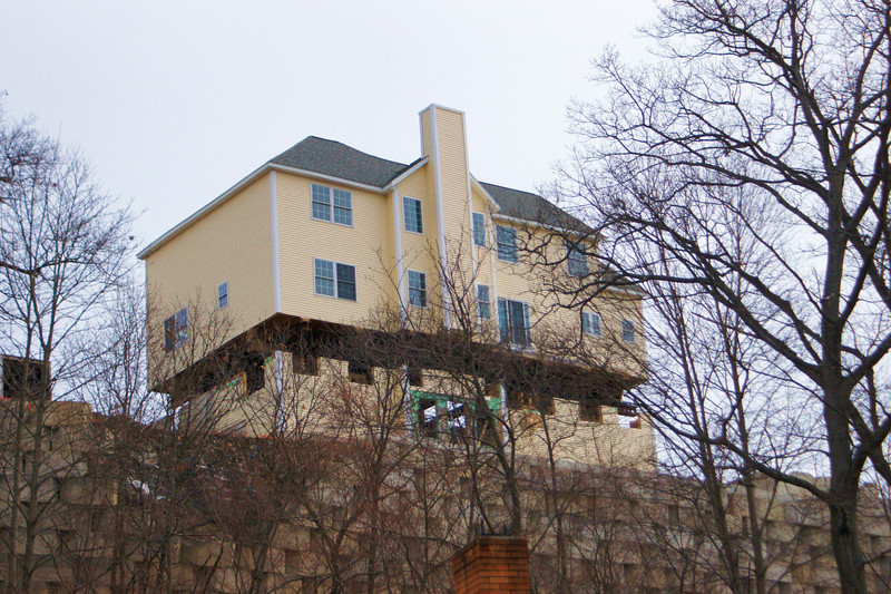 High rise: A house is lifted off of it's foundation and moved 1/4 mile away from the collapsing retaining wall.
