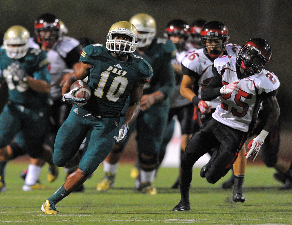. Long Beach Poly football takes on Centennial (Corona) as part of the Mission Viejo Classic in Mission Viejo, CA on Friday, September 13, 2013. Poly\'s James Brooks finds a hole to run through as he begins a 73-yard run to set up a TD. (Photo by Scott Varley, Press-Telegram)