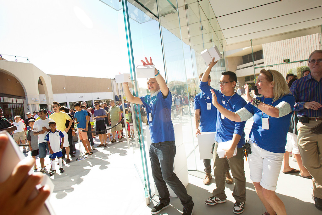 . Apple store staff, right, welcome shoppers to the redesigned Apple Store at the Stanford Shopping Center in Palo Alto, Calif., on Saturday, Sept. 7, 2013.  (LiPo Ching/Bay Area News Group)