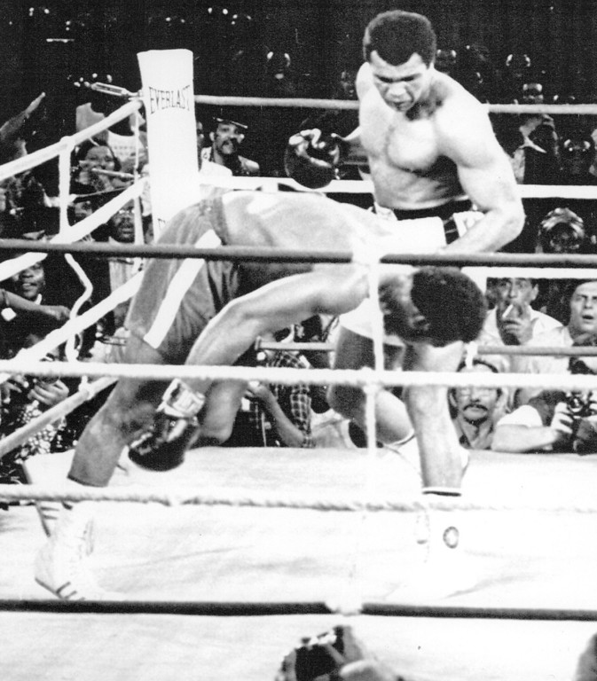 . Ali wins Back The Crown--George Foreman Falls toward the canvas as his defense of the world heavy weight title ends in an eighth-round knockout by Muhammad Ali Oct. 30 in Kinshasa, Zaire. 1974. Credit: AP Wirephoto
