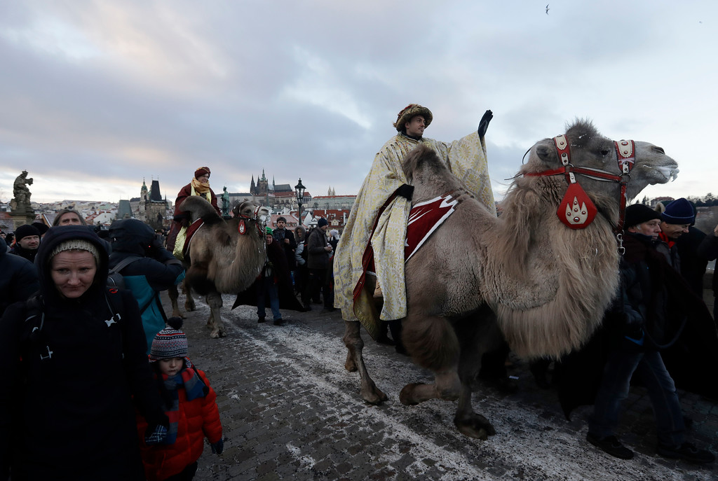 . Men dressed as the Three Kings ride on camels during a procession of the Three Kings across the Charles Bridge in Prague, Czech Republic, Friday, Jan. 6, 2017. The procession, which annually marks the end of the Christmas festivities in Prague, is a re-enactment of the journey of the Three Kings to visit the infant Jesus. Prague Castle is in the background. (AP Photo/Petr David Josek)