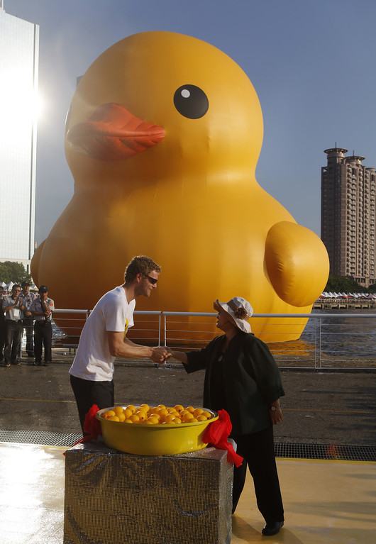 . Dutch conceptual artist Florentijin Hofman is photographed with Kaohsiung City Mayor Cheng Chu near his creation of a giant Rubber Duck at Glory Pier on September 19, 2013 in Kaohsiung, Taiwan. The \'Rubber\' Duck,\' is traveling the world and will stop in Kaohsiung from September 19 to October 20.  (Photo by Ashley Pon/Getty Images)