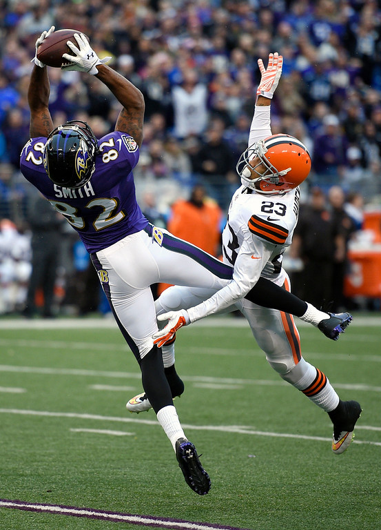 . Baltimore Ravens wide receiver Torrey Smith, left, pulls in a catch for a first down in front of Cleveland Browns cornerback Joe Haden in the second half of an NFL football game, Sunday, Dec. 28, 2014, in Baltimore. (AP Photo/Nick Wass)