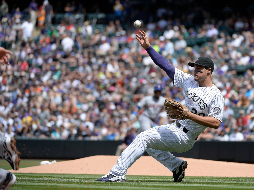. Colorado Rockies third baseman Nolan Arenado (28) throws the ball falling down to Colorado Rockies shortstop Charlie Culberson (23) to double up New York Mets second baseman Daniel Murphy (28) in the first inning May 4, 2014 at Coors Field. (Photo by John Leyba/The Denver Post)
