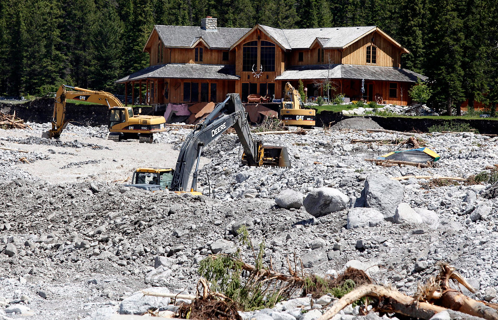 . Excavators work in Cougar Creek in Canmore, Alberta, Canada on Saturday, June 22, 2013, after floods ravaged the town.  (AP Photo/The Canadian Press, Jeff McIntosh)