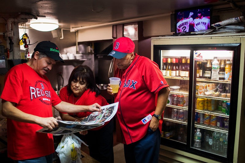 Avid Red Sox fans Armando Delgado, Carmen Castagena and Gerardo Santiago read the newspaper while the Red Sox play the Yankees on a television in the kitchen at El Mondonguito Puerto Rican restaurant and bar in Boston, Massachusetts on September 19, 2018. The bar is a favorite among Puerto Ricans in Boston where people flock to watch their team play under the new management of fellow Puerto Rican Alex Cora. For the New York Times