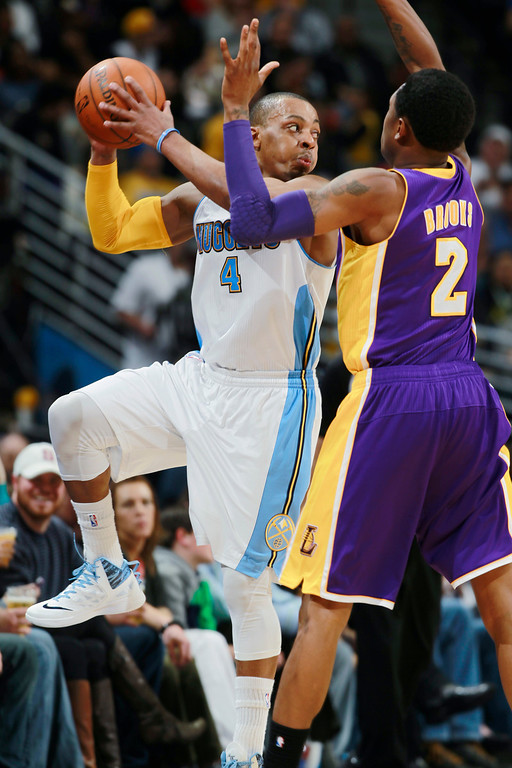 . Denver Nuggets guard Randy Foye, left, pulls in a loose ball and looks to pass as Los Angeles Lakers guard MarShon Brooks covers in the third quarter of the Nuggets\' 134-126 victory in an NBA basketball game in Denver on Friday, March 7, 2014. (AP Photo/David Zalubowski)