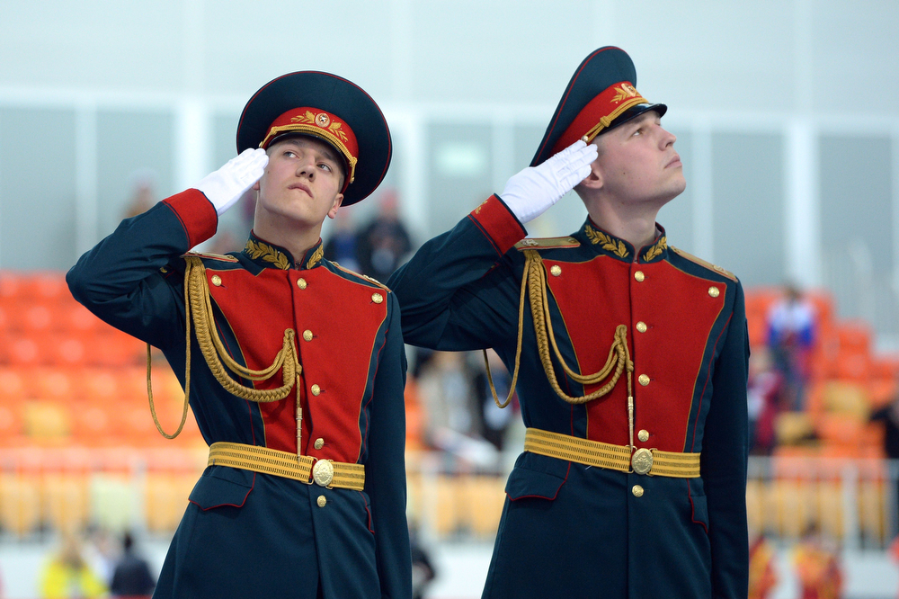 . Russian honor guards salute during the Women\'s Speed Skating Team Pursuit Medal Ceremony at the Adler Arena during the Sochi Winter Olympics on February 22, 2014. (JUNG YEON-JE/AFP/Getty Images)