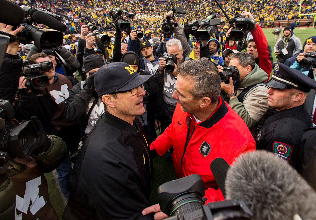 . Michigan head coach Jim Harbaugh, center left, shakes hands with Ohio State head coach Urban Meyer, center right, after an NCAA college football game in Ann Arbor, Mich., Saturday, Nov. 25, 2017. Ohio State won 31-20. (AP Photo/Tony Ding)