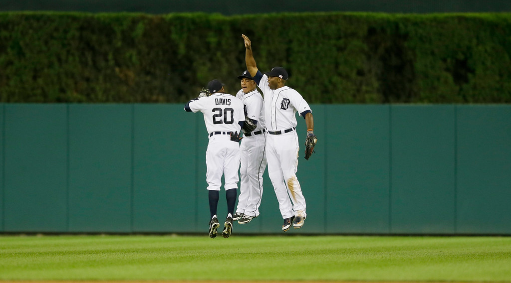 . Detroit Tigers outfielders Rajai Davis (20), Ezequiel Carrera, center, and Torii Hunter celebrate their 7-2 win over the Cleveland Indians in a baseball game in Detroit, Friday, Sept. 12, 2014. (AP Photo/Carlos Osorio)