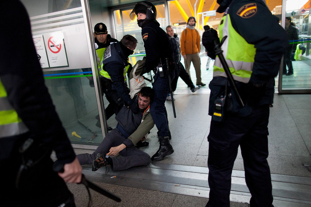 Description of . Policemen arrest a Spanish Airline Iberia worker during a protest against job cuts at Barajas Airport on February 18, 2013 in Madrid, Spain. Today is the first of a five day strike held by Iberia cabin crew, maintenance workers and ground staff in response to the planned loss of 3,800 jobs. The strike has resulted in the airline having to cancel 400 flights this week with unions planning a further five day strikes within a month.  (Photo by Pablo Blazquez Dominguez/Getty Images)