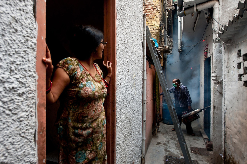 . In this picture taken on October 3, 2013, an Indian woman (L) watches as a municipal health worker (back R) fumigates against mosquitoes at a neighborhood in New Delhi. Dengue fever is a mosquito-borne disease with no known cure or vaccination that strikes fear into the citizens of New Delhi when it arrives with the monsoon rains -- just as the scorching heat of the summer is subsiding.  MANAN VATSYAYANA/AFP/Getty Images