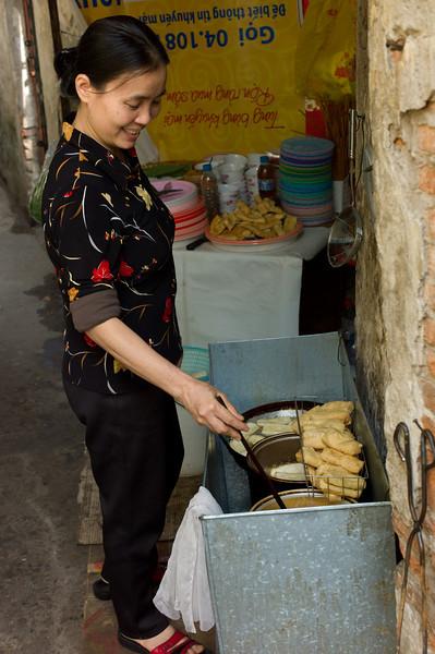A back alley chef preparing deep fried somethings in Hanoi, Vietnam.