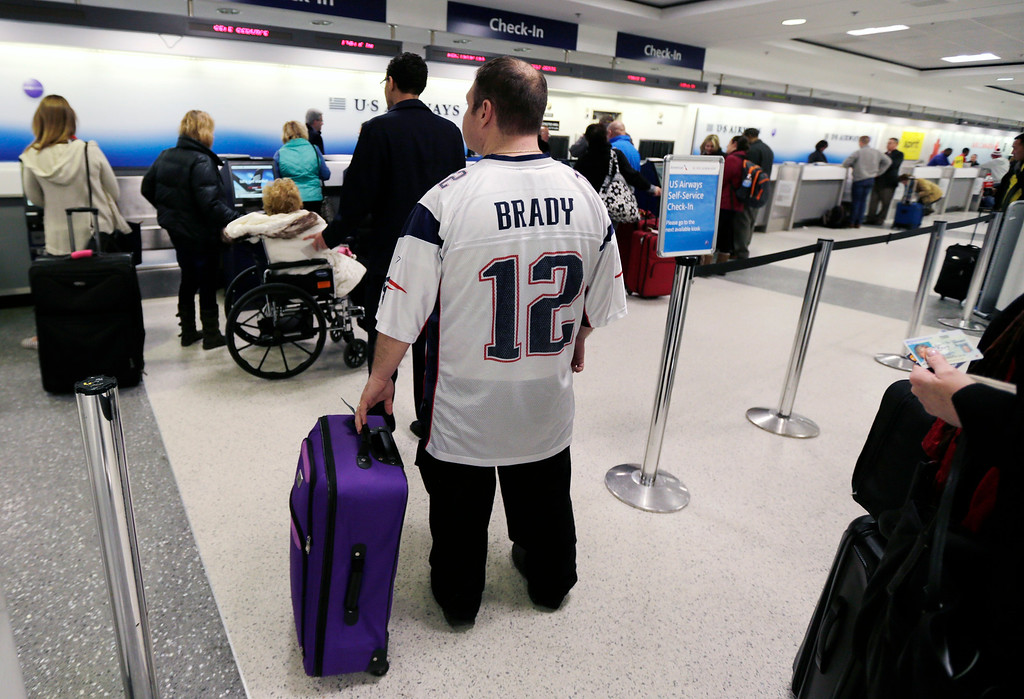 . New England Patriots fan Anthony Monaco, of the South Boston neighborhood of Boston, waits in line for his flight to Phoenix, at Logan Airport in Boston, Monday, Jan. 26, 2015.  Monaco, who has Super Bowl tickets, hopes to fly out of the Boston before a winter storm that is expected to hit the area with about two feet of snow in the winter storm.   (AP Photo/Charles Krupa)