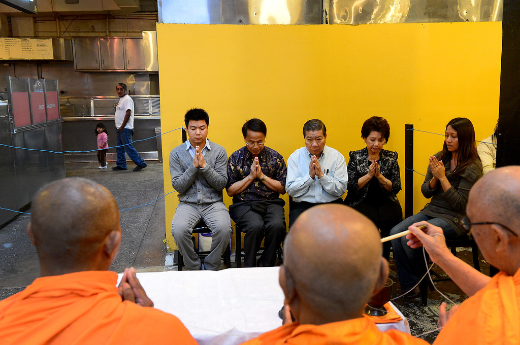 . David Tewasart, left, of Pasadena, and his family follow along in prayer as Wat Thai Temple monks, of North Hollywood, bless the opening of his restaurant Sticky Rice at Grand Central Market in downtown Los Angeles Monday, April 30, 2013.  (SGVN/Staff Photo by Sarah Reingewirtz)