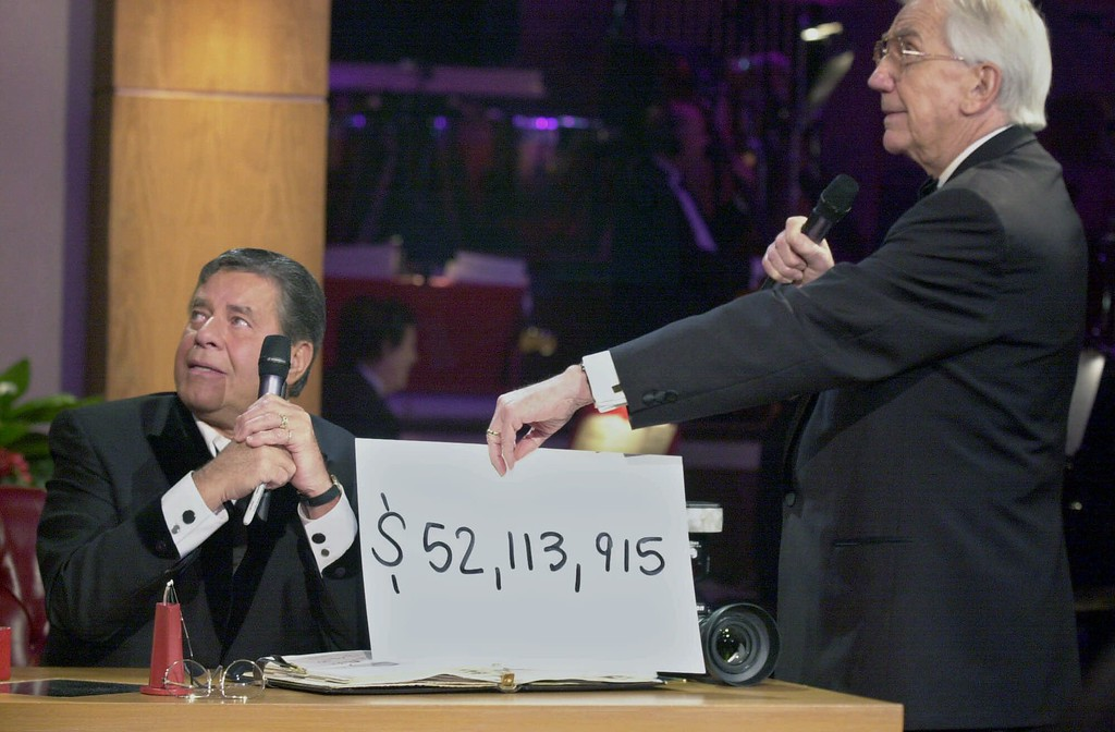 . File - With the tote board no longer working, Ed McMahon brings out a card for host Jerry Lewis to learn the current amount of money raised during the final hour of Lewis\' 35th annual telethon for muscular dystrophy, Monday, Sept. 4, 2000, in Los Angeles. The telethon raised pledges of $54,610,289 in 21 1/2 hours. (AP Photo/Kim D. Johnson)