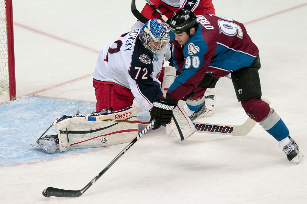 . Colorado Avalanche\'s  Ryan O\'Reilly (90) can\'t get a shot off around Columbus Blue Jackets goalie Sergei Bobrovsky (72), of Russia, during the first period of an NHL hockey game on Monday, April 15, 2013 in Denver. (AP Photo/Barry Gutierrez)