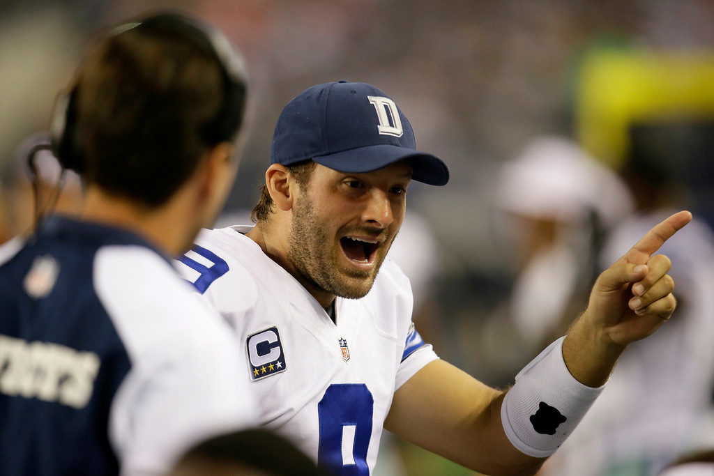 . Dallas Cowboys quarterback Tony Romo (9) talks with teammates on the bench after the Cowboys scored against the Washington Redskins in the first half of an NFL football game, Sunday, Oct. 13, 2013, in Arlington, Texas. (AP Photo/Tim Sharp)