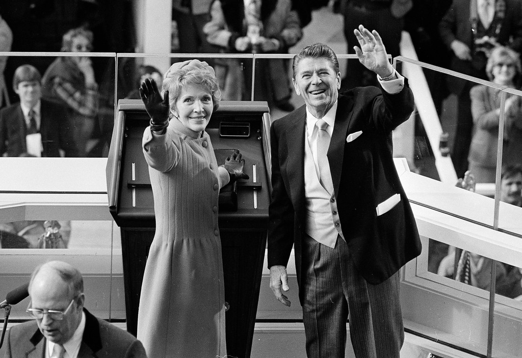 . FILE - In this Jan. 20, 1981, file photo, President Ronald Reagan and first lady Nancy Reagan wave to onlookers at the Capitol building as they stand at the podium in Washington following the swearing in ceremony. The inauguration of the U.S. president is traditionally a highly-scripted celebration, with seating charts, schedules, dress rehearsals, and planning committees that map each moment of the history-making day from start to finish. But sometimes the unexpected happens.  It was the first inaugural on the terrace, and the west front has been used ever since. But what happened minutes later made this Inauguration Day different from so many before _ Iran freed 52 American hostages it had held for 444 days. A complicated deal, worked out in the final weeks of the Carter administration, eventually secured their freedom. Reagan, however, announced to the nation that the hostages were on their way home.  (AP Photo, File)