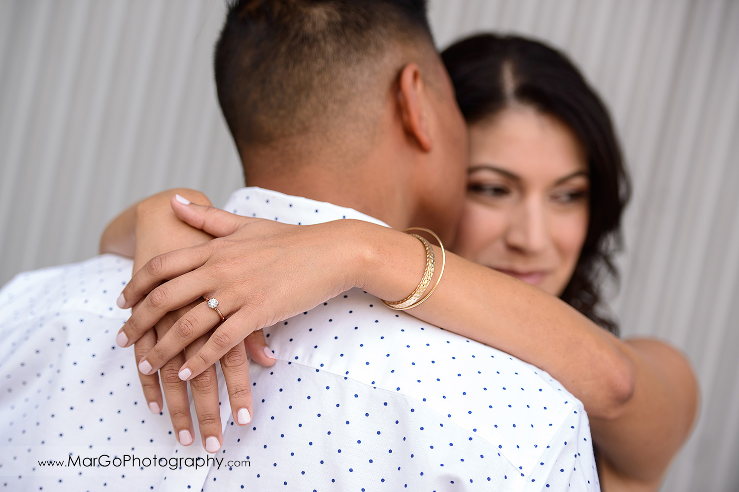 ring shot of woman in blue dress holding hands on neck of man in white shirt during engagement session at San Pedro Square Market in San Jose