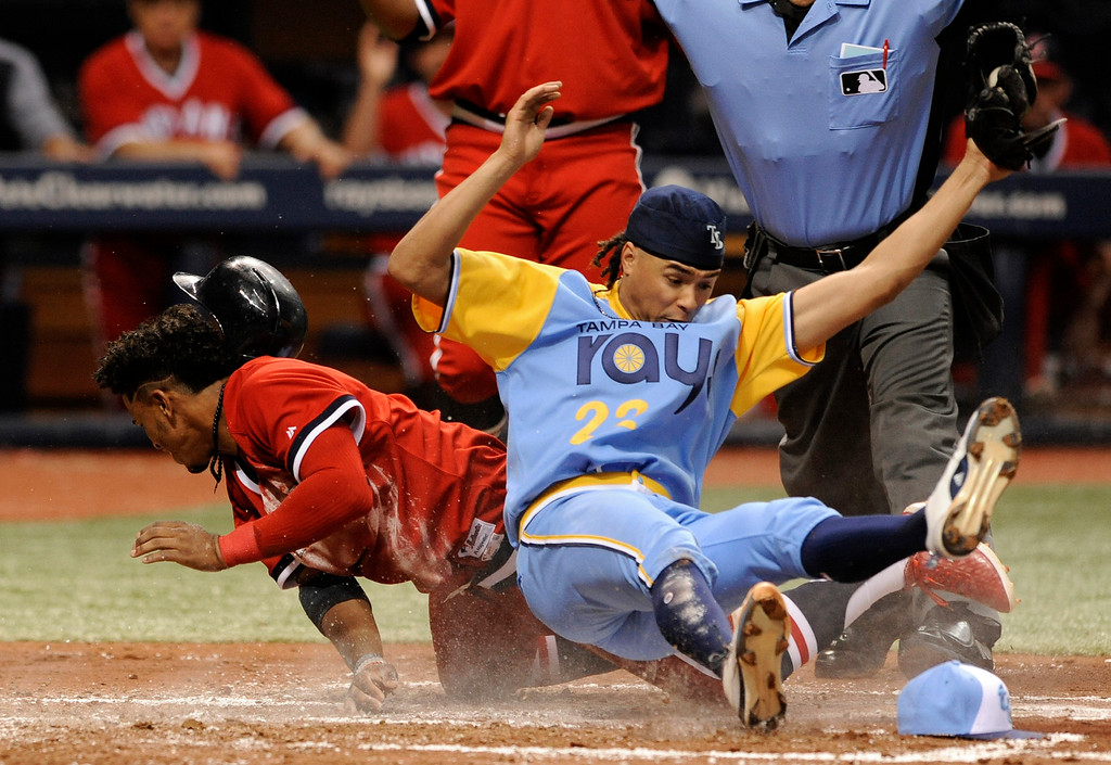 . Cleveland Indians\' Francisco Lindor, left, scores on a wild pitch from Tampa Bay Rays starter Chris Archer, right, during the third inning of a baseball game Saturday, Aug. 12, 2017, in St. Petersburg, Fla. Archer was covering the plate on the throw from catcher Wilson Ramos. (AP Photo/Steve Nesius)