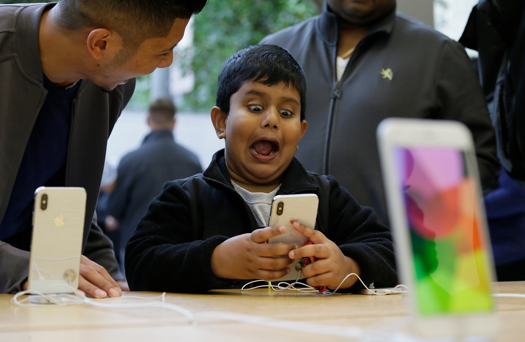 . Aadhyan Vaka, 6, of Plainsboro, N.J., reacts while playing with the animoji feature of the new iPhone X at the Apple Union Square store Friday, Nov. 3, 2017, in San Francisco.  (AP Photo/Eric Risberg)