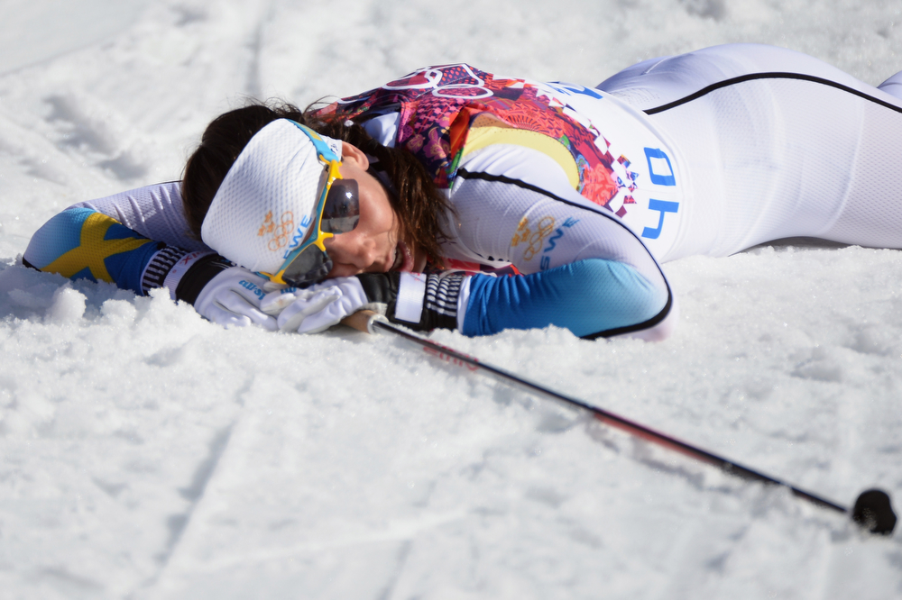 . Charlotte Kalla of Sweden collapses at the finish line after coming in second in the Women\'s 10 km Classic during day six of the Sochi 2014 Winter Olympics at Laura Cross-country Ski & Biathlon Center on February 13, 2014 in Sochi, Russia.  (Photo by Harry How/Getty Images)