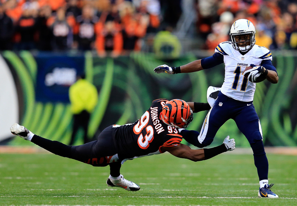 . Wide receiver Eddie Royal #11 of the San Diego Chargers runs with the ball as defensive end Michael Johnson #93 of the Cincinnati Bengals defends during a Wild Card Playoff game at Paul Brown Stadium on January 5, 2014 in Cincinnati, Ohio.  (Photo by Rob Carr/Getty Images)