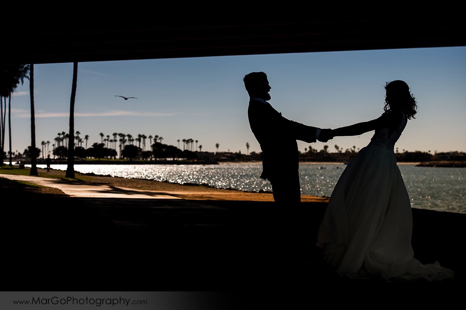 silhouette of bride and groom under the bridge at San Diego Mission Bay Park