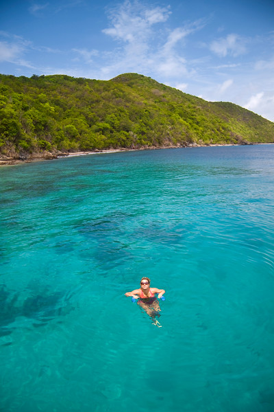 Young woman floating in crystal clear tropical water next to island.