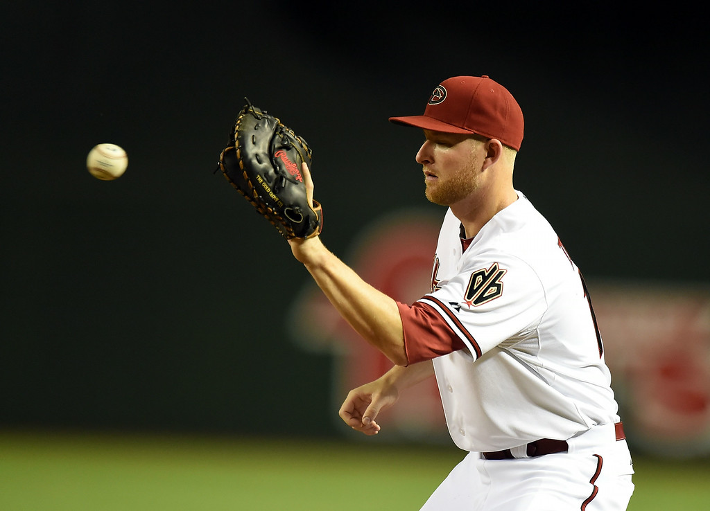. Mark Trumbo #15 of the Arizona Diamondbacks catches a throw while covering first base during the fourth inning against the Colorado Rockies at Chase Field on August 8, 2014 in Phoenix, Arizona.  (Photo by Norm Hall/Getty Images)