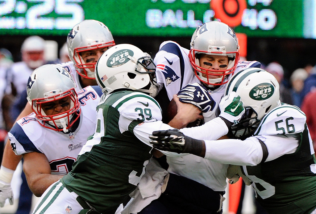 . New York Jets cornerback Antonio Allen (39) and Demario Davis (56) sack New England Patriots\' Tom Brady, second from right, during the first half of an NFL football game Sunday, Dec. 21, 2014, in East Rutherford, N.J. (AP Photo/Bill Kostroun)