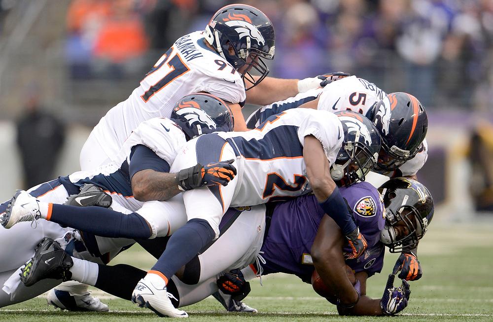 . Denver Broncos defensive tackle Kevin Vickerson (99) Justin Bannan (97) Wesley Woodyard (52) and Champ Bailey (24) gang tackle Baltimore Ravens fullback Vonta Leach (44) during the first quarter Sunday, December 16, 2012 at M&T Bank Stadium. John Leyba, The Denver Post